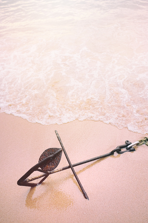 An anchor on the beach with soft wave and sea form. Photo with vintage style filter and sand, old rose color.