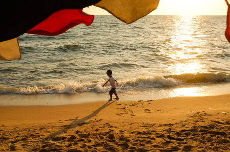 A boy playing with small waves on the beach at Jomtien beach, Pattaya, Chonburi, Thailand. 版權商用圖片