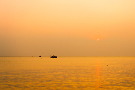 The sunset with fi​shing boat in the Gulf of Thailand, Bang Saen, Chonburi, Thailand. Фото со стока - 104564932