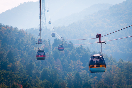Cable car flying over the beautiful autumn to the top of Mireuksan Mountain