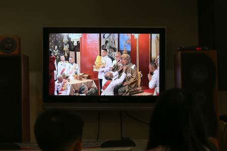 Bangkok, Thailand, May 4, 2019: A Thai girl watching the Royal Coronation via live TV at her home. His Majesty the King attends the Song Muratha Bhisek or Royal Purification ceremony.