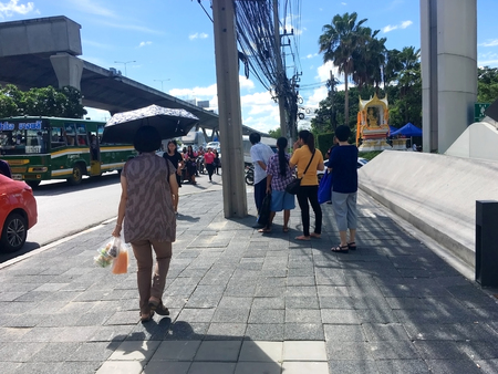 Bang Na, Bangkok  Thailand – June 10, 2019: Daily life in Bangkok. People waiting for a bus under shado​w of the ele​ctr​ic pole, someone walking with an umb​rell​a in the sunn​y day.