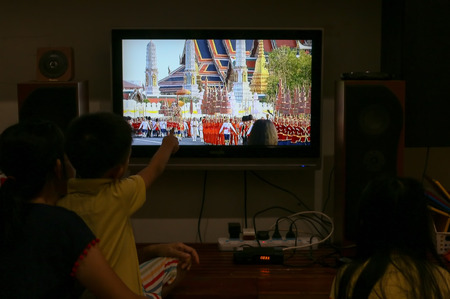 Royal Procession – Bangkok, Thailand, May 5, 2019: A Thai family watching the Royal Coronation via live TV at their home. His Majesty King Maha Vajiralongkorn's seven-kilometre​​ Royal Land Procession Фото со стока - 128785541