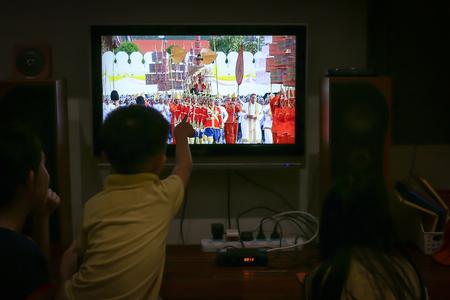 Royal Procession – Bangkok, Thailand, May 5, 2019: A Thai family watching the Royal Coronation via live TV at their home. His Majesty King Maha Vajiralongkorn's seven-kilometre Royal Land Procession