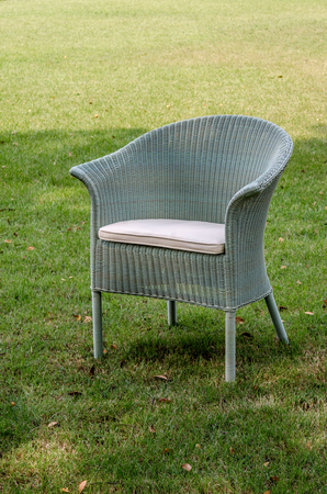 grey water: Grey water resistant rattan chair with cushion in the garden Stock Photo