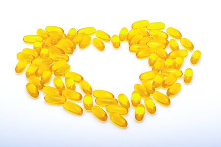 yellow heart: Fish oil capsules, vitamins yellow, heart shaped on white background Stock Photo