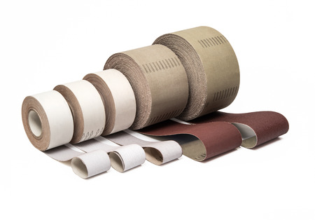 Sandpaper in rolls for industrial use in different sizes and thickness on white background