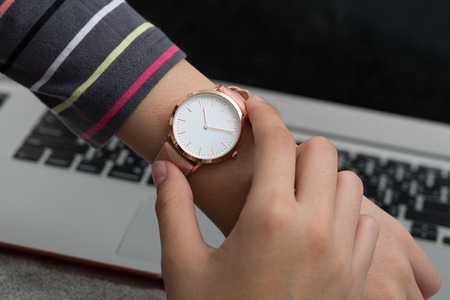 Girl's hand with wrist watch in front of notebook computer