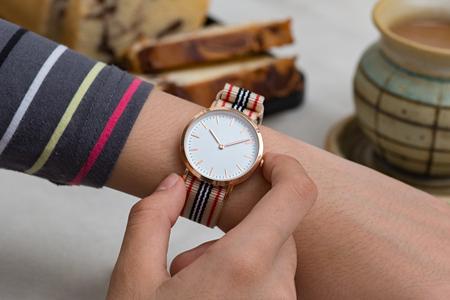 puntualidad: Mano de chica con relojes de pulsera en la pausa para el café en frente de chocolate caliente y pastel Foto de archivo