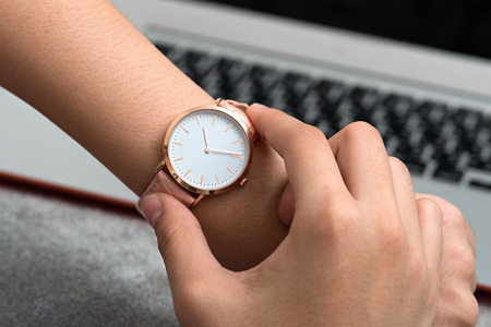 tardy: Girls hand with wrist watch in front of desk with notebook computer