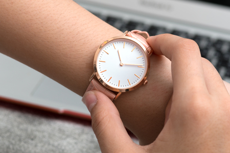 Girls hand with wrist watch in front of desk with notebook computer