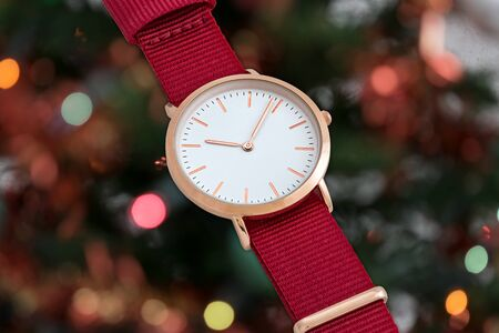 Red nylon strap wrist watch in Christmas time in front of Christmas tree lights background Stock Photo