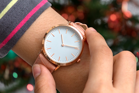 Girls hand with wrist watch in Christmas time in front of Christmas tree in background Stock Photo