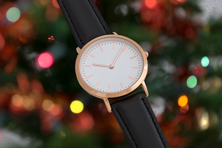 Black leather strap wrist watch in Christmas time in front of Christmas tree lights background Stock Photo