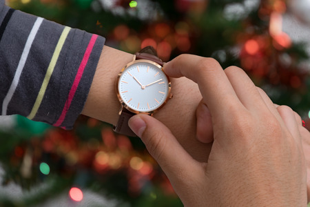 Wrist watch on girls hand in christmas time in front of a Christmas tree in background