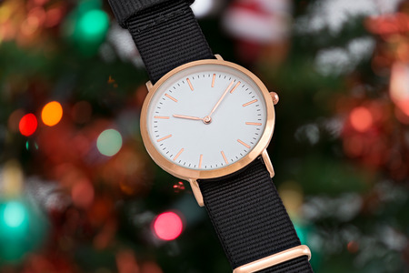 Wrist watch with black nylon strap in Christmas time in front of Christmas tree lights background Stock Photo