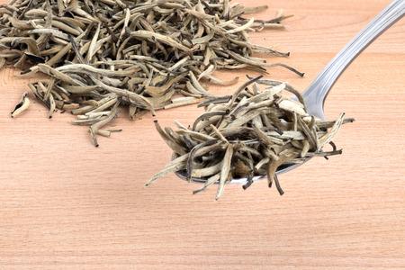 White needle tea on wooden cutting board