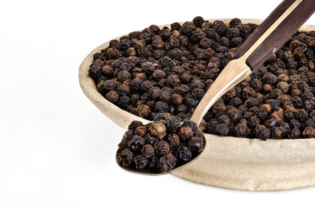 Whole Black Pepper in Old stone bowl and on Spoon Zdjęcie Seryjne