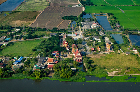 Buddhist temple, farm land, rice fields farmland in Thailand aerial photo