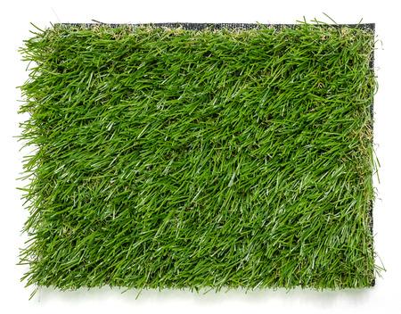 pasto sintetico: Estera de hierba sobre fondo blanco. Fondo de azulejos de césped artificial.