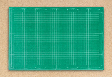 Green cutting mat on brown paper background with clipping path.