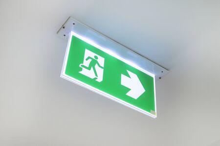 Znak wyjścia pożarowego. Drzwi ewakuacyjne ewakuacyjne na suficie. Zielony znak ewakuacyjny wskazujący drogę do ucieczki.