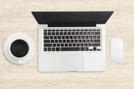 Laptop computer and a cup of coffee on wooden table. Top view business background.