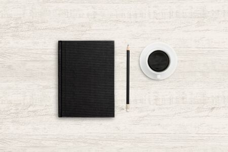 Top view business background of notebook and coffee cup on wooden texture.