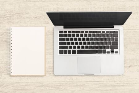 Laptop computer and blank notebook on wooden table. Top view business background.
