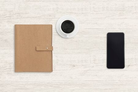 Smartphone with notebook and a cup of coffee on wood background.