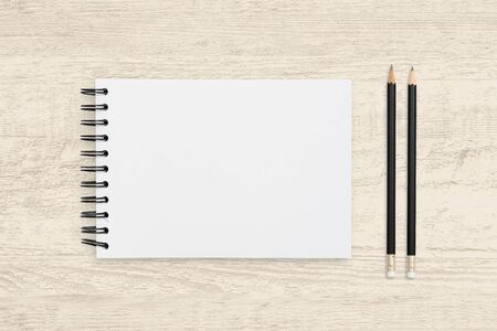 Top view object background of blank notebook and pencil on wooden texture background.