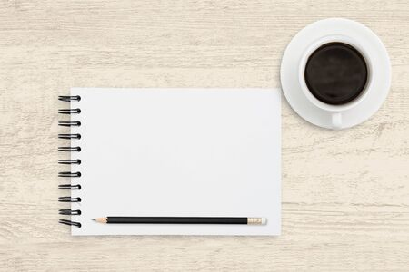 Top view business background of white paper sheet of notebook with coffee cup on wooden texture background. Reklamní fotografie