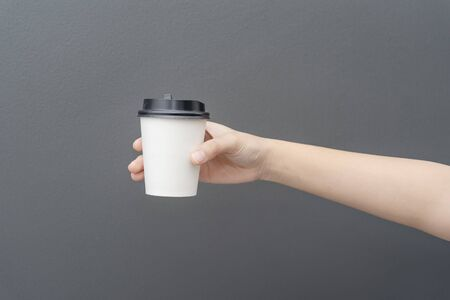 Take away coffee cup background. Female hand holding a coffee paper cup on gray background Reklamní fotografie - 134728729