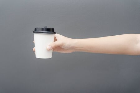 Take away coffee cup background. Female hand holding a coffee paper cup on gray background