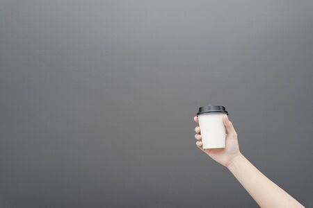 Take away coffee cup background. Female hand holding a coffee paper cup on gray background Reklamní fotografie - 134729712