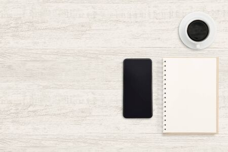 Smartphone with notebook and a cup of coffee on wood background. Reklamní fotografie - 134729932