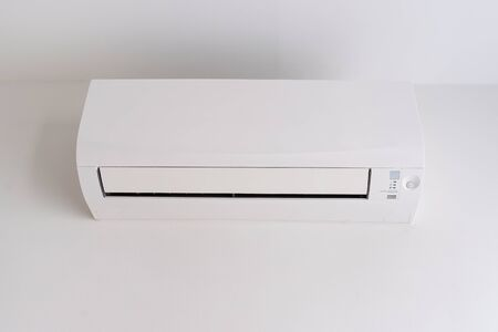 Air conditioner on white concrete wall in area of room space.