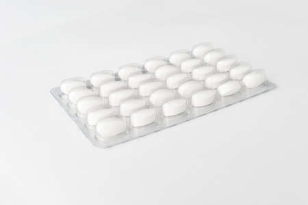 White pills tablets in package on a white background. Capsule pills in plastic pack for pharmacy and medicine background.