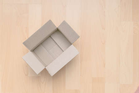 Empty open rectangular cardboard box on wood background. Shopping online object background. Shipping parcel object.