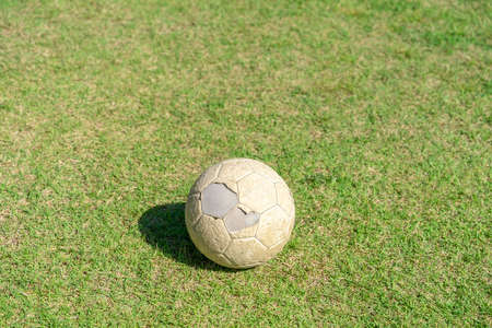 Old soccer ball on green grass of soccer field. Vintage football.