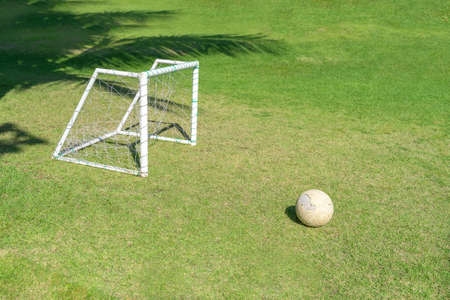 Soccer ball in grass field in front of the goal post. Football ball on green grass of playground.