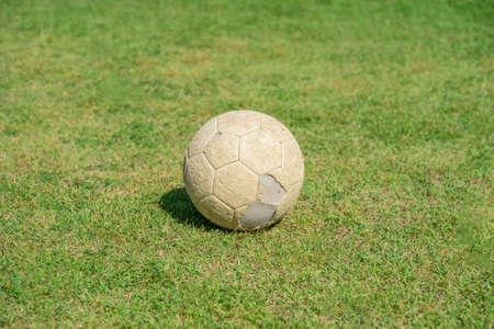Old soccer ball on green grass of soccer field. Vintage football.