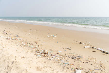 Trash on tropical Beach. Plastic pollution environmental problem. Plastic bottles and other garbage washed up on beach.