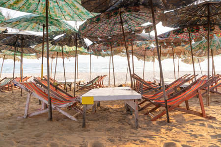 Beach chairs in vacation area. Beach loungers on deserted coast sea. 版權商用圖片