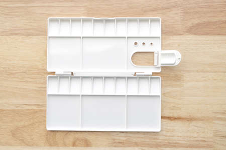 White watercolour palette. Empty watercolor tray isolated on wood background. White plastic paint palette.