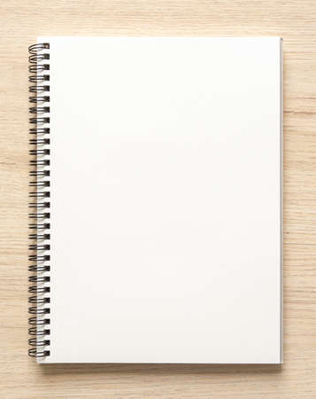 Blank spiral bound notepad mockup template with Kraft Paper cover, isolated on wood background. High resolution.