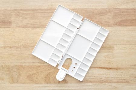 Empty watercolor palette background. White plastic paint palette. Watercolor tray on wood background. Stockfoto