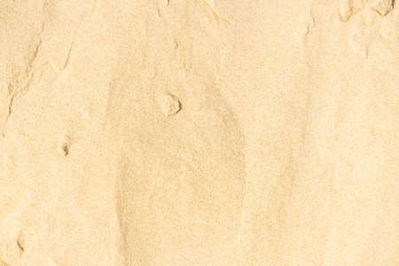 Sand texture on the beach. Brown beach sand for background. Close-up.