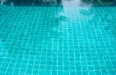Part of swimming pool and turquoise tile with blue water. Standard-Bild