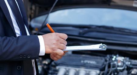 Seitenansicht des Schreibens auf Klemmbrett während Untersuchungsauto des Versicherungsagenten Standard-Bild